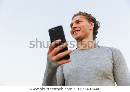 View from below of Smiling Curly Sportsman holding smartphone Stock photo © deandrobot