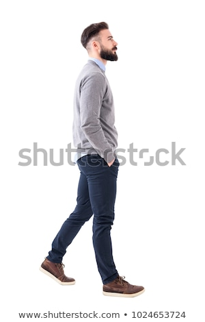 relaxed young business man is walking with hand in pocket stock photo © feedough