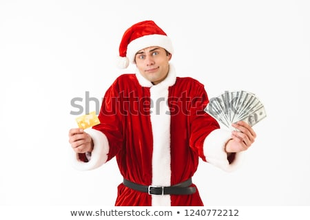 image of caucasian man 30s in santa claus costume holding dollar stock photo © deandrobot