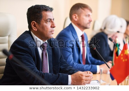 Mature serious politician listening to one of colleagues Stock photo © pressmaster