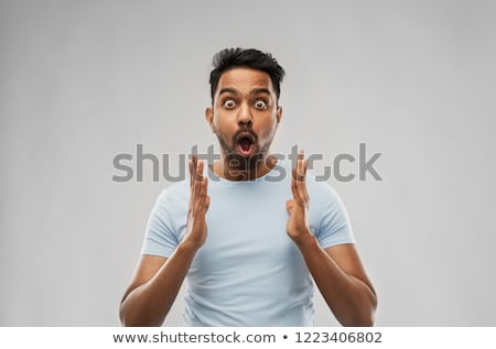 shocked indian man over grey background Stock photo © dolgachov