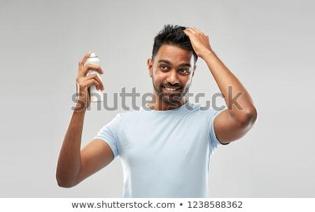 smiling indian man applying hair spray over gray Stock photo © dolgachov