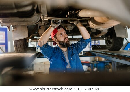Serious worker in workwear standing under broken car and examining its motor Stock photo © pressmaster