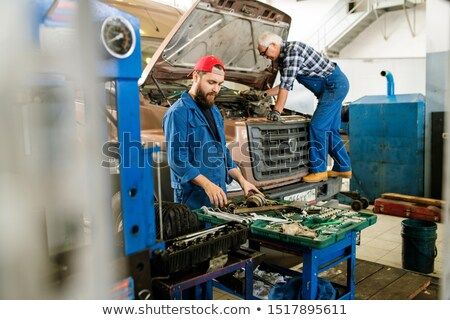 Young repairman in workwear standing by open kit with variety of worktools Stock photo © pressmaster