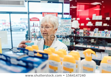 Saleslady in drug store sorting thru her goods in the shelves Stock photo © Kzenon