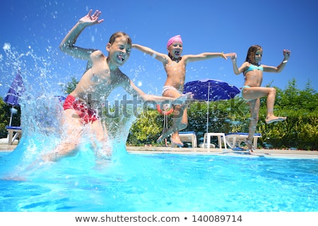 two young boys friends jumping in the pool stock photo © galitskaya