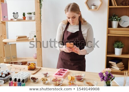 Young woman with smartphone taking photo of handmade soap in silicone molds Stock photo © pressmaster