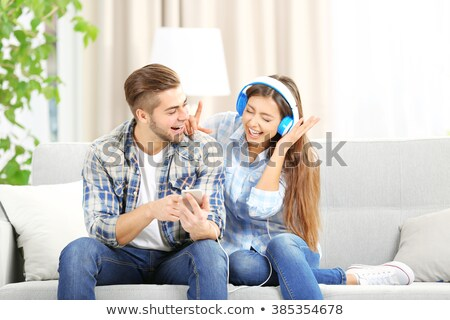 couple with gadgets listening to music at home Stock photo © dolgachov