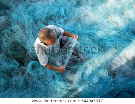 Fisherman cleaning fish Stock photo © olira