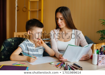 Portrait of adult woman watching as her son doing homework Stock photo © HASLOO