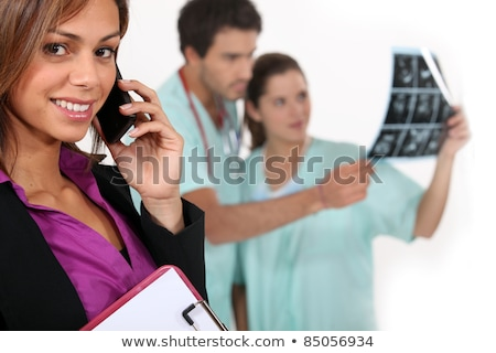 Hospital manager on a phone as medics look at x rays in the background Stock photo © photography33