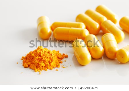 A handful of  turmeric capsules with the contents of one spilled stock photo © SophieJames