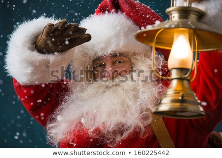 Santa Claus is holding a shining lantern outdoors at North Pole  Stock photo © HASLOO