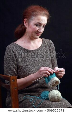 Smiling middle age woman knitting on spokes at home Stock photo © dashapetrenko