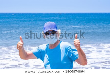 smiling man on the beach making the ok sign stock photo © feedough