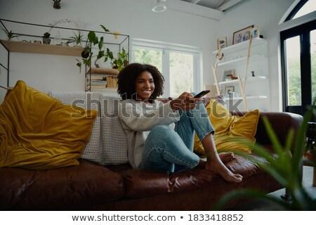 женщину · диване · молодые · улыбаясь · женщины · наушники - Сток-фото © dash
