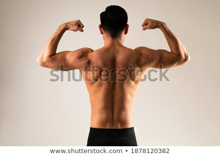 back view portrait of muscular man showing his biceps stock photo © deandrobot