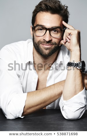 Handsome man in glasses unbuttoning shirt Stock photo © deandrobot