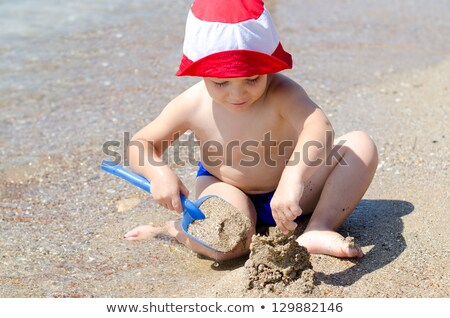 boy enjoys digging at the beach Stock photo © meinzahn