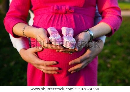pregnant woman outdoor with pink baby shoes in her hands stock photo © kb-photodesign
