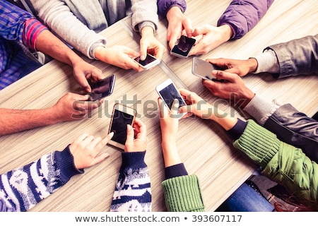 Friends sitting in cafe and using mobile phone. stock photo © deandrobot