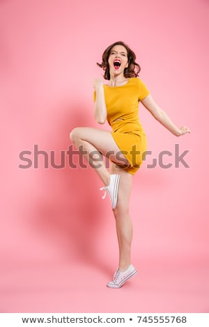 Happy young woman showing fists and looking at camera Stock photo © deandrobot