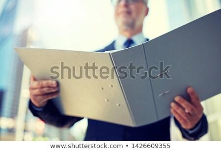 senior businessman with ring binder folder in city Stock photo © dolgachov