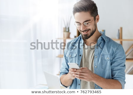 Smiling bearded man in shirt holding smartphone Stock photo © deandrobot