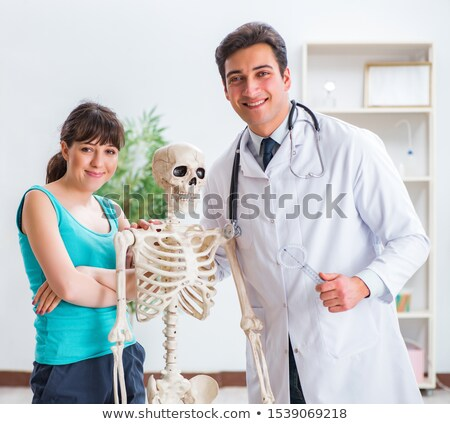 Doctor showing type of injury on skeleton to patient Stock photo © Elnur