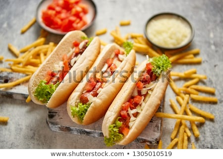 Assortment of three tasety hot dogs, placed on wooden cutting board Stock photo © dash