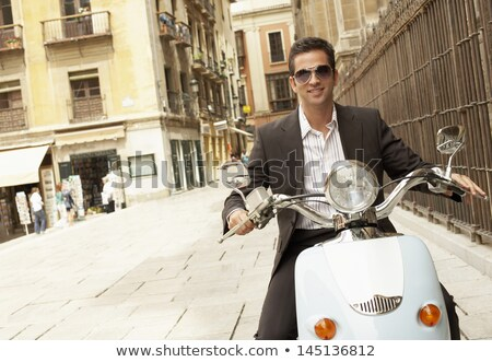 Feliz jovem empresário equitação motocicleta ao ar livre Foto stock © deandrobot