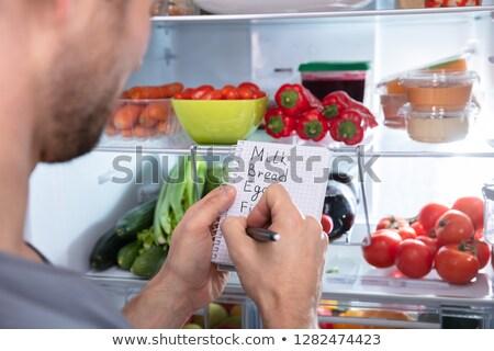 man writing on spiral notepad near refrigerator stock photo © andreypopov