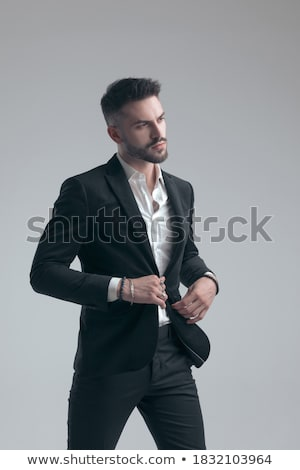 young businessman buttoning his black suit while stepping forwar Stock photo © feedough