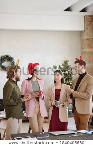 Group of four cheerful smartly dressed friends standing Stock photo © deandrobot
