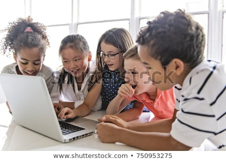 Group of curious children watching stuff on the laptop screen Stock photo © Lopolo