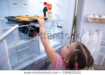 Girl Trying To Reach Out And Pick Cupcakes From Fridge Stock photo © AndreyPopov