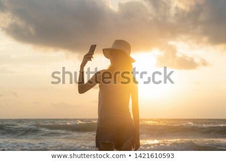 Giovani Asia donna cellulare spiaggia tramonto Foto d'archivio © galitskaya