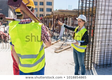 Female foreman coordinating and guiding workers on the construction site Stock photo © Kzenon