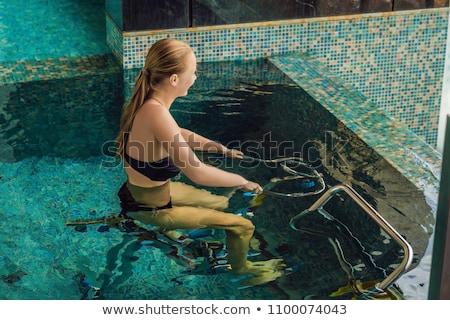 Young woman on bicycle simulator underwater in the pool ストックフォト © galitskaya