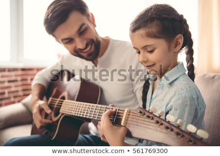 Cute little girl and her handsome father are playing guitar and  Stock photo © boggy