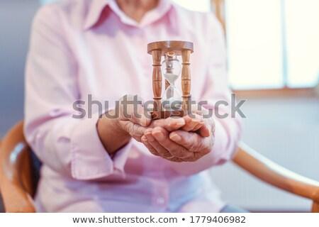 Senior in nursing home holding a hourglass - time is running up Stock photo © Kzenon