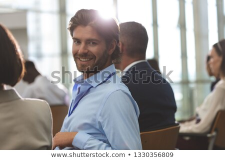 Portrait of happy young Caucasian businessman looking at camera during seminar in office building Stock photo © wavebreak_media