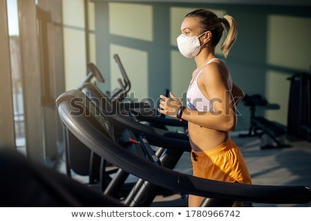 Young woman running on treadmill during sports training in a gym Stock photo © boggy