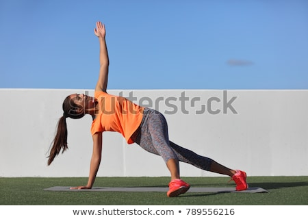 Yoga pose variation fitness girl doing the fallen triangle assited with leg. Asian woman doing side  Stock photo © Maridav