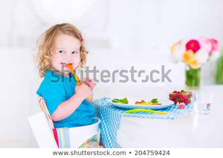 young child eating tomatoes in high chair stock photo © gewoldi