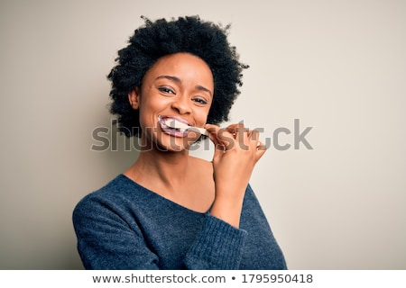 closeup portrait of a woman brushing her teeth stock photo © dash