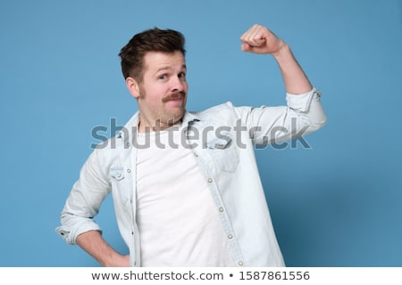 smiling man is showing his fist stock photo © meinzahn