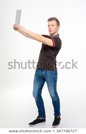 Amusing concentrated young man making selfie using tablet Stock photo © deandrobot