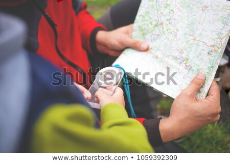 Stockfoto: Man Sitting And Looking At Maps In His Hands