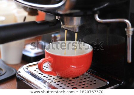 Espresso running in glass on professional coffee maker Stock photo © Kzenon